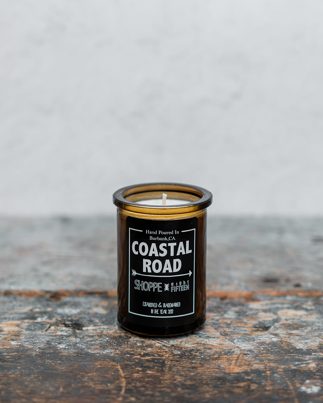 Coastal Road amber glass candle on wooden shelf