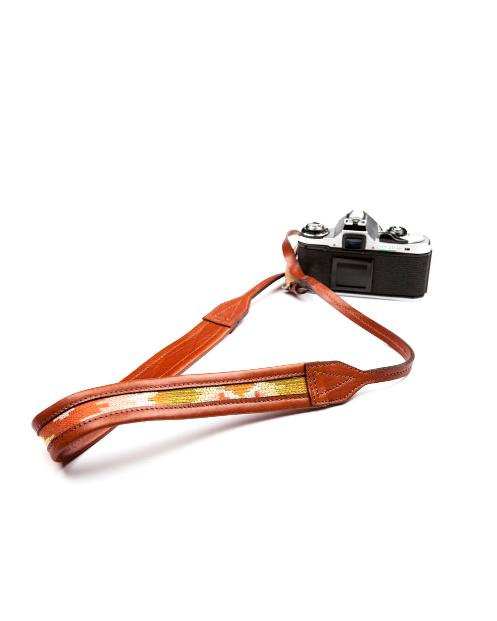 Camera with leather camera strap sitting on table