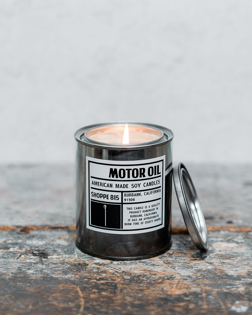 Lit Motor Oil gender neutral tin candle on wooden shelf