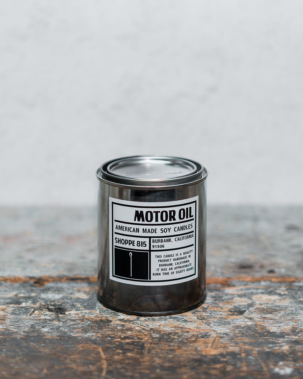 Motor Oil gender neutral tin candle on wooden shelf