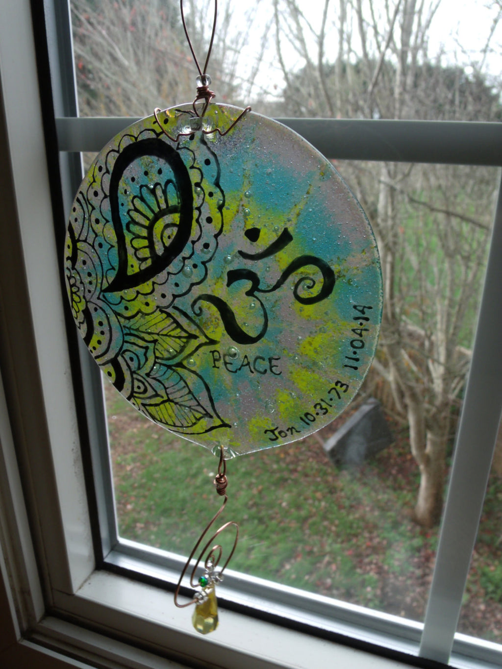 Ashes Infused Glass Cremation Art Sun Catcher OM Peace Memorial in a window