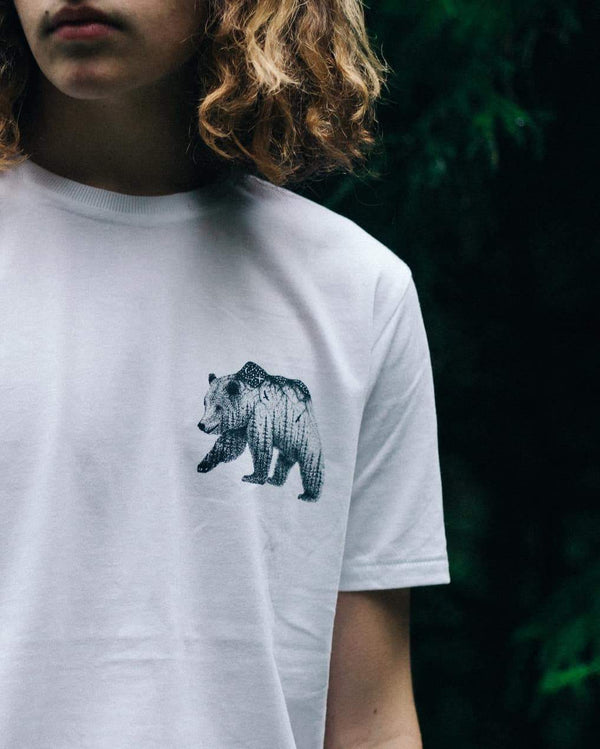 Man with midlength wavy hair wearing an Illustrate 'The Wandering Bear' t-shirt