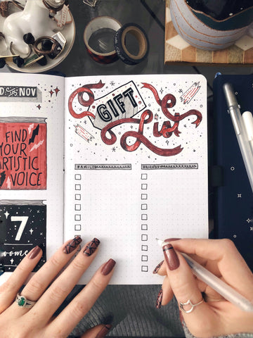 "An open bullet journal with the words ""Gift List"" at the top, with two female hands resting on the pages and holding a pen."