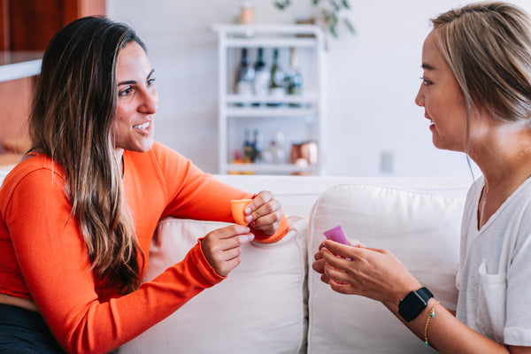 Photograph of two friends chatting. Each has a menstrual cup in their hands.