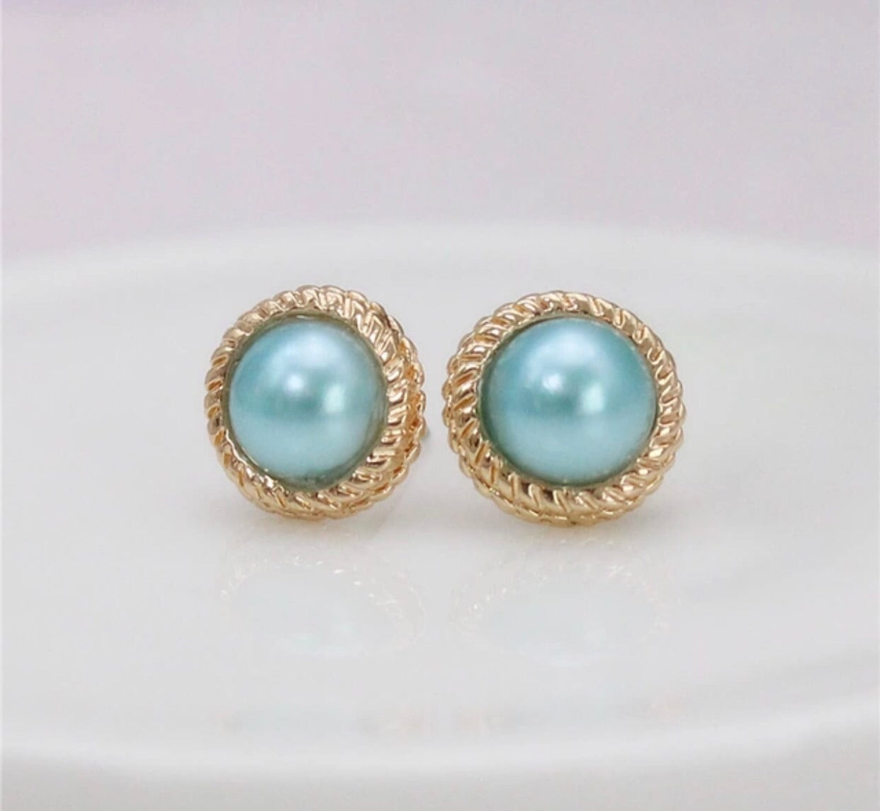 Pearl stud earrings with a gold frame