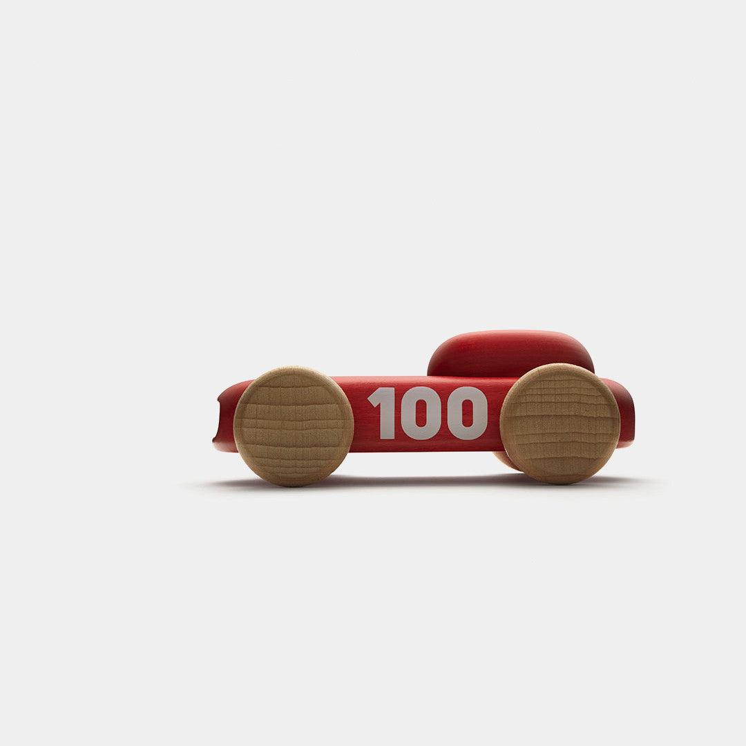 Permafrost's red wooden 100 racer car toy seen from the side