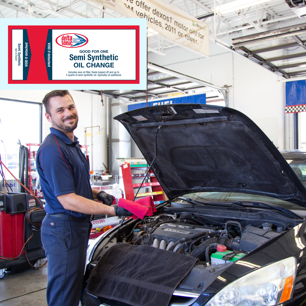 Image of Delta Sonic employee performing Semi-Synthetic oil change on a car.