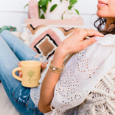 Gold Beaded stacking bracelets with initial disc zodiac charms on model with coffee mug - Blooming Lotus Jewelry