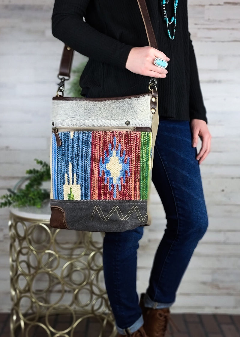 Large crossbody shoulder bag with grey cowhide at the top of the front of the bag and multi color southwestern print, with brown leather accents and shoulder strap, with solid tan canvas back and back zipper pocket, taken inside on white table with floral décor