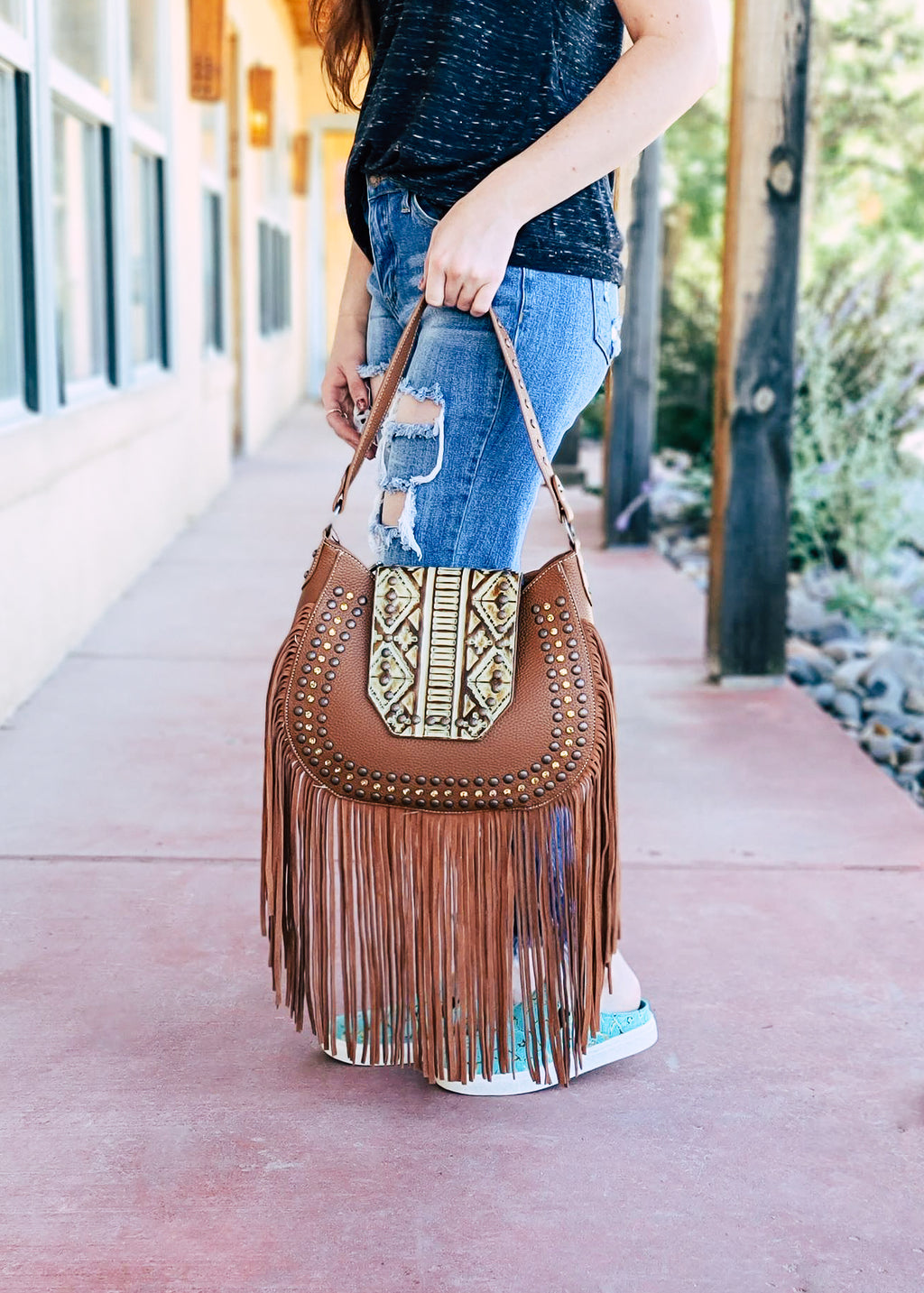 Brown Medium Handbag with Tan Rustic Aztec Design and Brown Rhinestones, with Long Strands of Fringe and 1 Shoulder Strap, Taken with Outside Lighting, on Brunette model