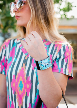black faux leather large snap on wrist cuff with turquoise horse design on blonde model