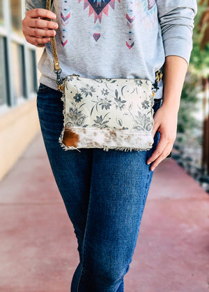 Small Ivory and Beige Crossbody with Floral Print and Cowhide with Brown Crossbody Strap on Blonde Model Taken Outside in Natural Light
