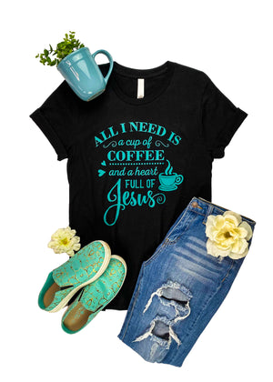 "Black Graphic Tee with ""All I Need Is A Cup Of Coffee And A Heart Full Of Jesus"" Printed in Teal Ink, Laid Flat on White Surface"