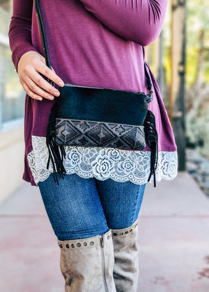 Black Cowhide Aztec Clutch Crossbody Handbag with bottom embossed aztec design on blonde model taken outside in natural light with slight edit