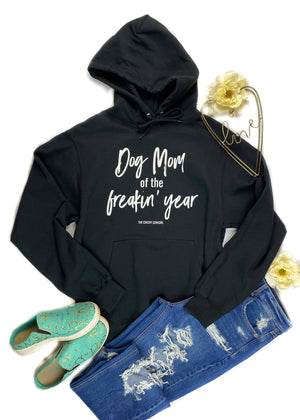 Black Dog Mom of the Freakin' Year Hoodie with white ink, laid flat on white surface with floral décor