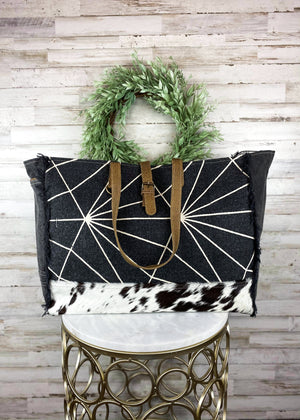 Large Black Weekender with White Abstract Lines and Black and White Cowhide, Brown Leather Accents and Shoulder Straps Taken Inside on White Table with Studio Lights and Green Plant Accents