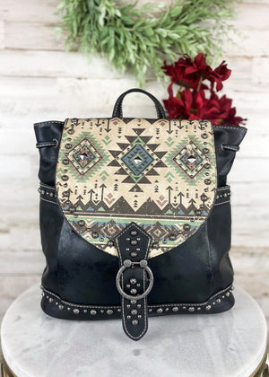 Black large backpack with flap over closure with Tan and multi-color Aztec print, with gun metal studs and hardware, 2 side pockets, taken inside on white table with floral décor
