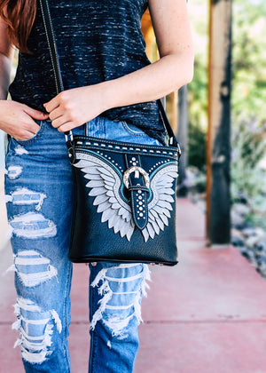 Black Studded Wing Crossbody Taken Outside in Natural Lighting on Brunette Model