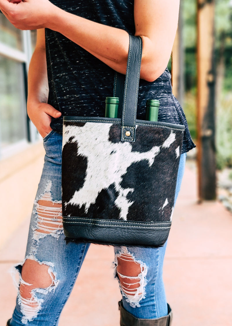 Black & White Cowhide 2 Bottle Caddy With Black Leather Handle, Taken On Blonde Model Outside