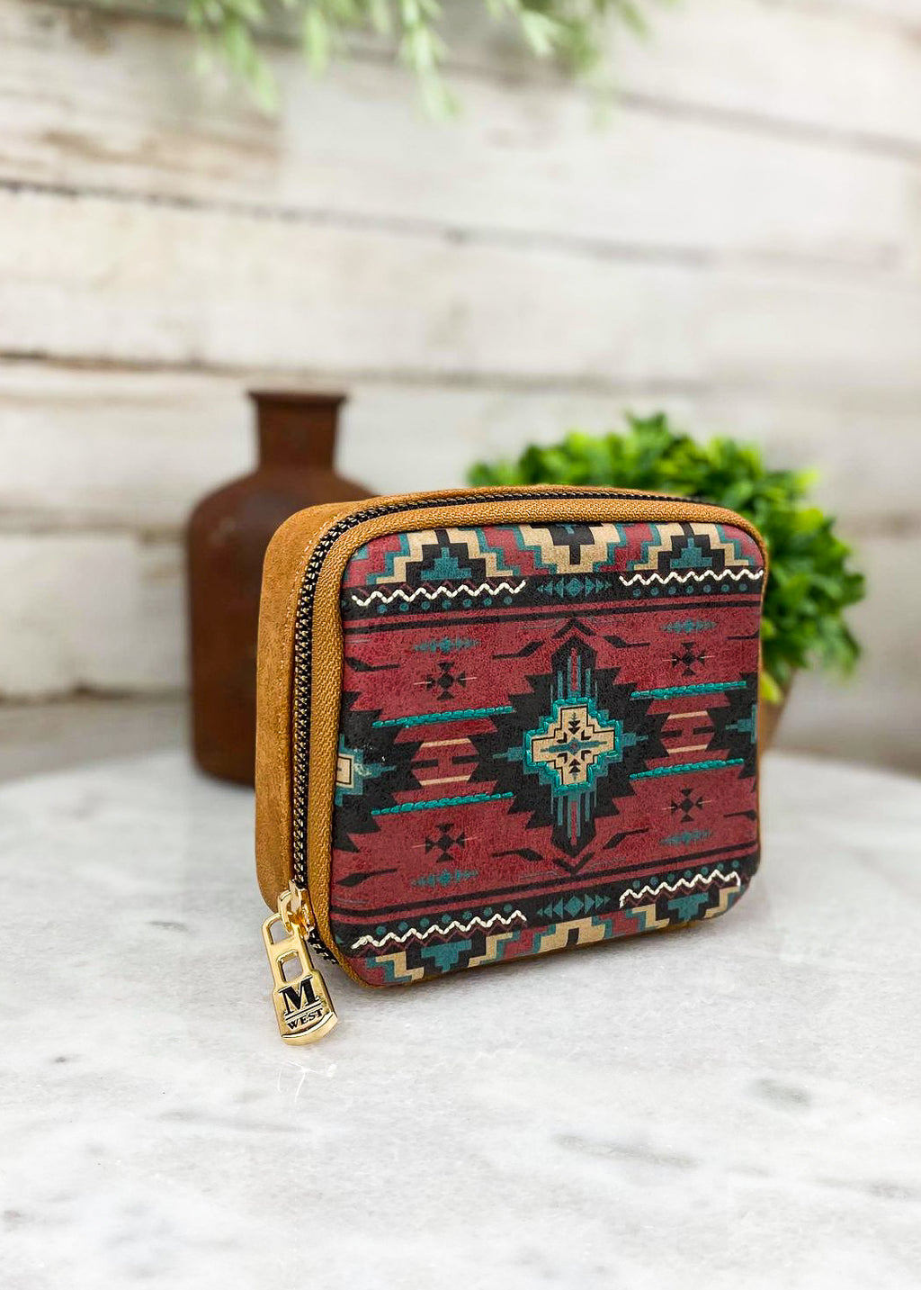 Small brown and multi color aztec pill and accessory travel case with zip around closure and plain brown leather on back taken inside on white table with green floral décor