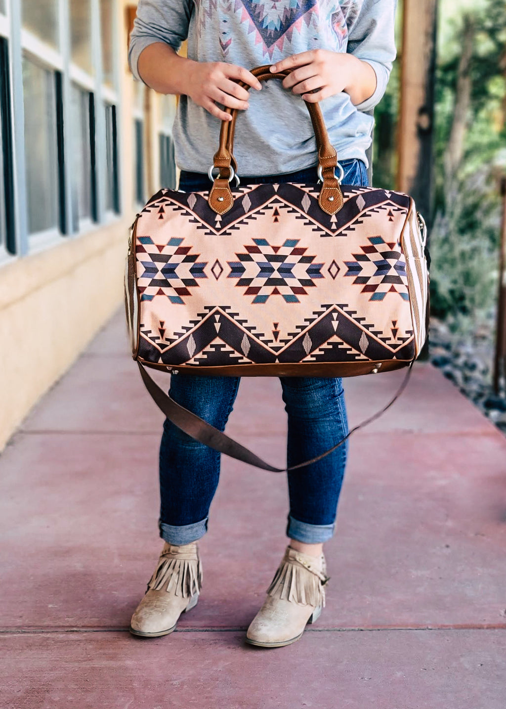 Brown and Ivory Weekender Bag with Warm Multi Color Aztec Print, with 2 Straps and a Crossbody Strap, on Blonde Model, Taken Outside in Natural Lighting