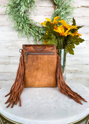 Back of Small Brown Crossbody with Brown Fringe on Sides and Aztec Print Flap Over Closure with Silver Concho Detail with Back Zipper Pocket