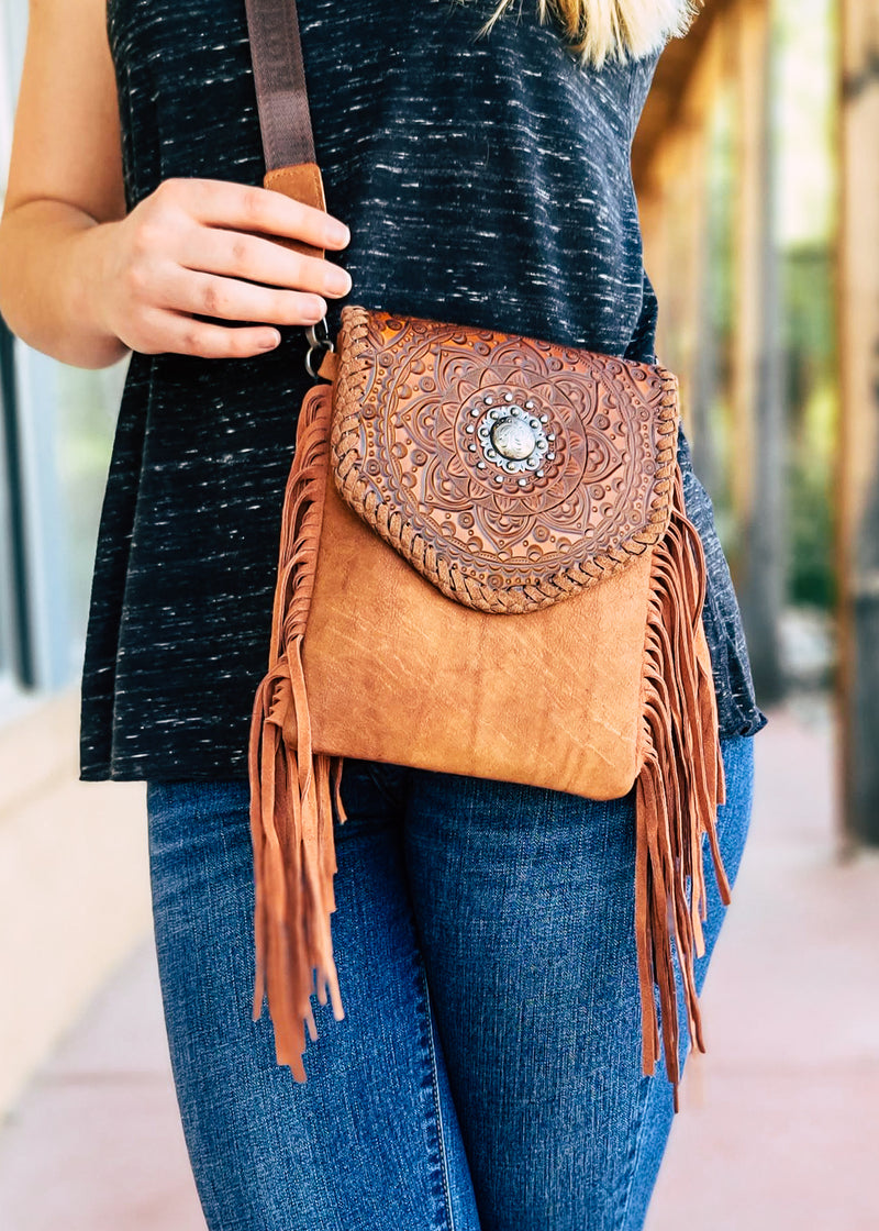 Small Brown Crossbody with Brown Fringe on Sides and Aztec Print Flap Over Closure with Silver Concho Detail on Blonde Model Taken Outside in Natural Light