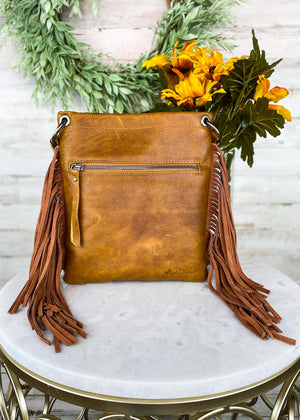 Back of Medium Brown Crossbody with Embossed Teal Aztec Pattern and Brown Fringe on the Sides and Back Zipper Pocket