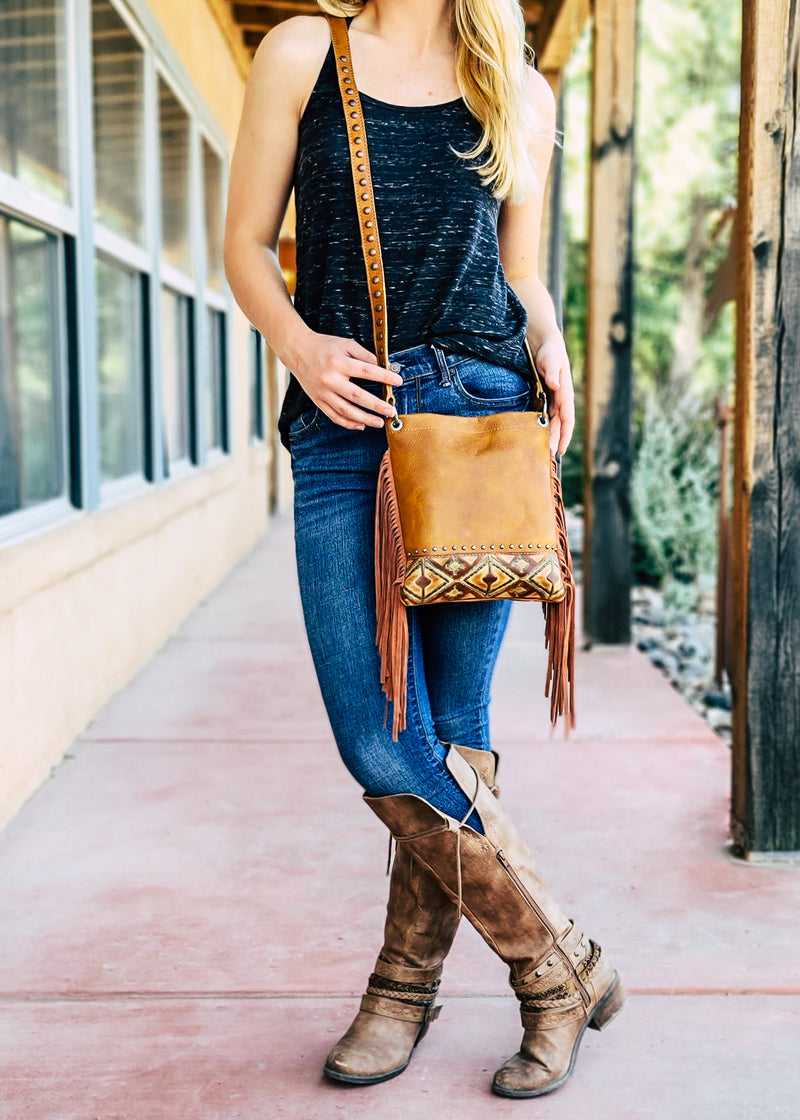 Medium Brown Crossbody with Embossed Teal Aztec Pattern and Brown Fringe on the Sides on Blonde Model Taken Outside in Natural Light