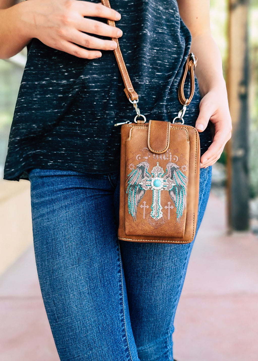 "Small Brown Crossbody with Cell Phone Pocket and Cross, Wings and ""Faith"", on Blonde Model Taken Outside in Natural Light"