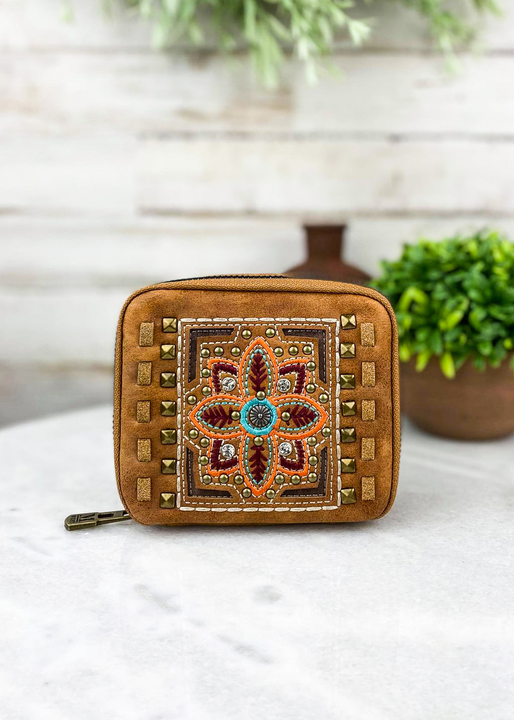 Small brown floral embroidered pill and accessory travel case with zip around closure and plain brown leather on back taken inside on white table with green floral décor