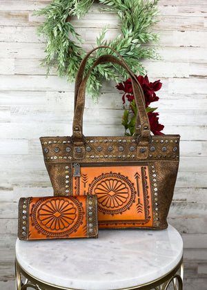 Brown large wide conceal carry handbag with orange aztec detail and gun metal concho hardware, with matching wallet, taken inside on white table with floral décor