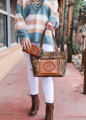 Brown large wide conceal carry handbag with orange aztec detail and gun metal concho hardware, with matching wallet, taken outside on model