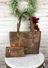 Back view of Brown large wide conceal carry handbag with orange aztec detail and gun metal concho hardware, with matching wallet, taken inside on white table with floral décor