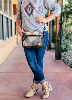 Small Brown Canvas and Leather Crossbody with Multi Color Aztec Print on Model Taken Outside in Natural Light