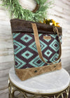 Medium sized handbag with brown leather straps and brown leather accents at the bottom, and purple and teal canvas Aztec Print and Brown cowhide at the top, taken on white table inside with studio lights and green floral décor accents