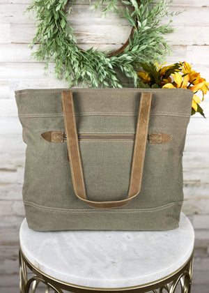 Back of Medium sized handbag with brown leather straps and a back zipper pocket, taken on white table inside with studio lights and green floral décor accents