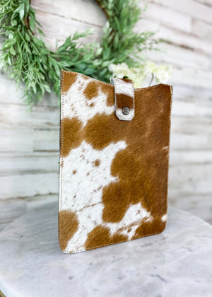 Side View of Brown and White Cowhide Tablet Sleeve with Flap Over Snap Button Closure, Taken Inside with Studio Lights and on White Table with Green Reef and White Flowers