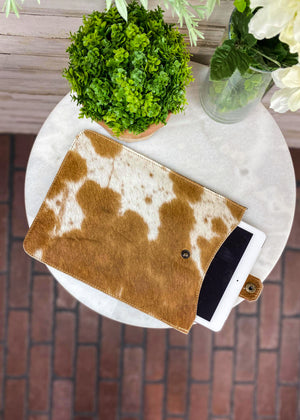 Brown and White Cowhide Tablet Sleeve with Flap Over Snap Button Closure, Taken Inside with Studio Lights and on White Table with Green Reef and White Flowers , Laid Flat with IPad Halfway Out