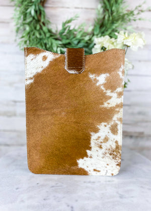 Back View of Brown and White Cowhide Tablet Sleeve with Flap Over Snap Button Closure, Taken Inside with Studio Lights and on White Table with Green Reef and White Flowers
