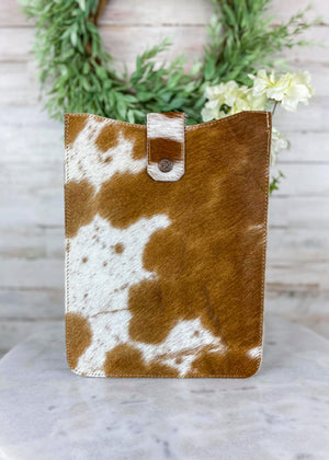 Brown and White Cowhide Tablet Sleeve with Flap Over Snap Button Closure, Taken Inside with Studio Lights and on White Table with Green Reef and White Flowers
