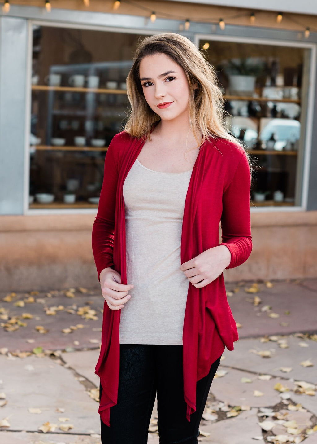 Burgundy long sleeve drape cardigan on blonde model with nude color camisole
