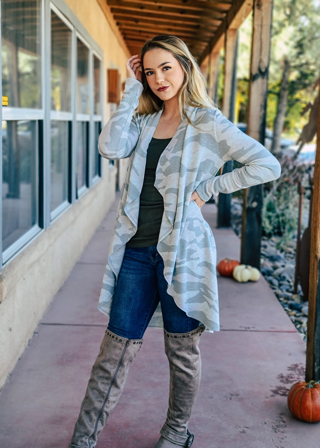 Light Grey Camo Drape Long Sleeve Cardigan on Blonde Model Wearing Denim Jeans and Taupe Knee High Boots Taken Outside in Natural Light