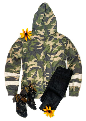 Back of Green Camo Long Sleeve Hoodie with 2 White Stripes on the Sleeves, Drawstrings, Laid Flat on White Surface with Black Pants and Black Shoes and Floral Accents