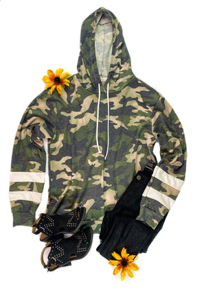 Green Camo Long Sleeve Hoodie with 2 White Stripes on the Sleeves, Drawstrings, Laid Flat on White Surface with Black Pants and Black Shoes and Floral Accents