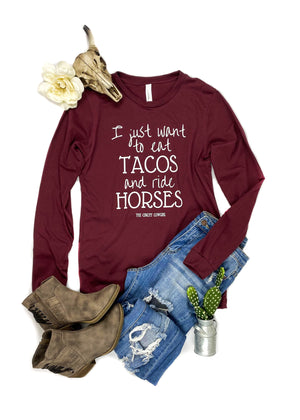 "SMALL Cardinal Red ""I Just Want To Eat Tacos and Ride Horses"" Long Sleeve Graphic Tee Laid Flat on White Surface with Distressed Jeans and Short Brown Boots, and Floral, Cactus, and Cowhead Décor"