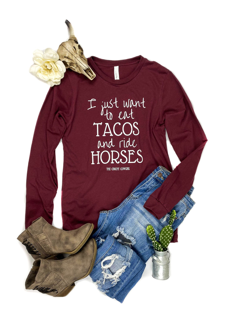 "Cardinal Red ""I Just Want To Eat Tacos And Ride Horses"" Long Sleeve Graphic Tee Laid Flat on White Surface with Distressed Jeans and Brown Short Boots and Floral and Cactus Décor"