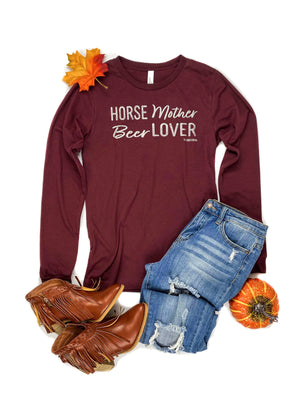 Cardinal Red Horse Mother Beer Lover Long Sleeve Graphic Tee Laid Flat on White Surface with Distressed Jeans and Brown Fringe Boots and Fall Décor Accents