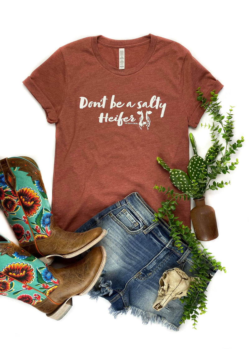 "Clay colored short sleeve graphic tee with ""Don't Be A Salty Heifer"" laid flat on white surface with floral décor"