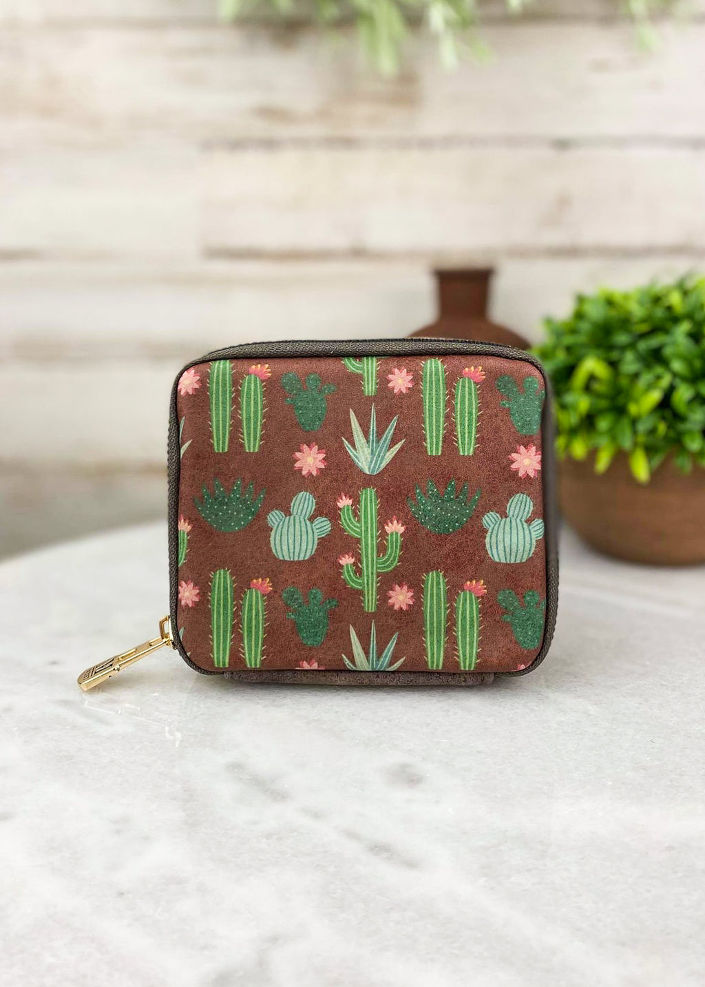 Small coffee colored with cactus print pill and accessory travel case with zip around closure and plain coffee leather on back taken inside on white table with green floral décor